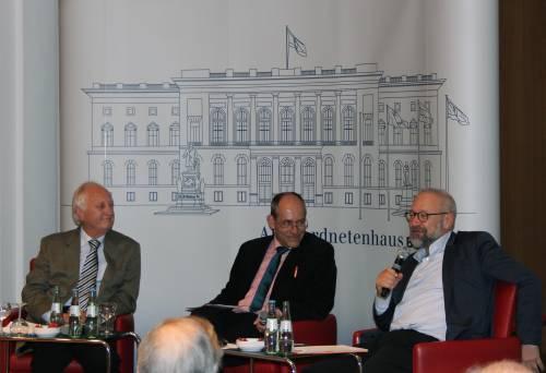 Drei Männer während einer Podiumsdiskussion. Sie sitzen auf roten Sesseln. Einer spricht ins Mikrofon. Die anderen schauen ihn an.
