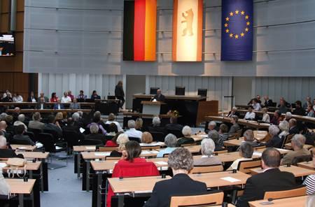 Menschen sitzen auf den Plätzen im Plenarsaal