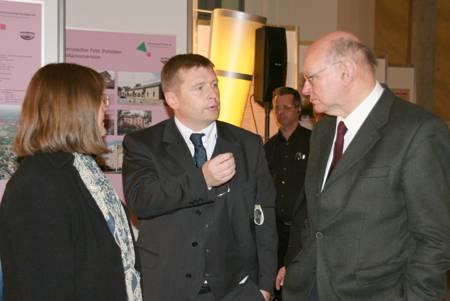 Zwei Männer und eine Frau im Gespräch während einer Ausstellung.