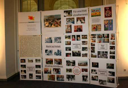 Eine Stellwand mit Ausstellungsplakaten und Bildern.