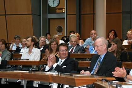 Blick in die Sitze des Plenarsaals. Menschen klatschen. Ein Mann vorne lacht, andere schauen ihn an.