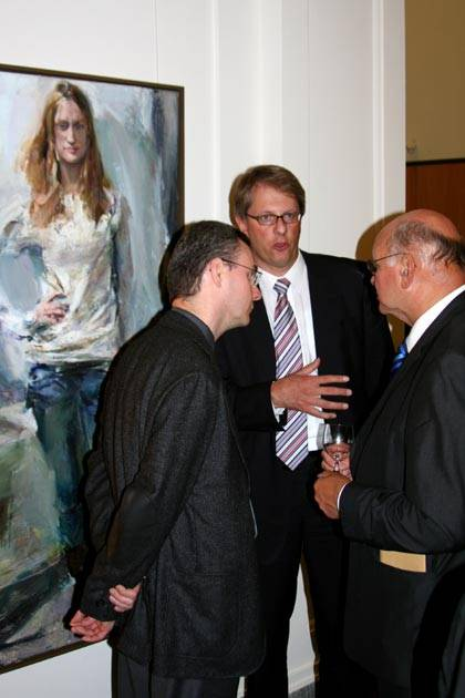 Drei Männer unterhalten sich vor einem Gemälde einer Frau.