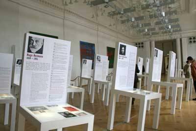 Viele Ausstellungsplakate in Form eines Holzstuhles