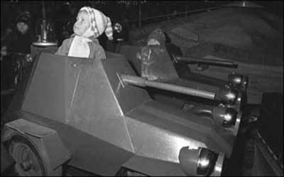 Ein Schwarz Weiß Foto eines Kindes in einem Miniaturpanzer.
