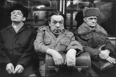 Ein Schwarz Weiß Foto von drei Männern in Winterjacken, die in einer Bahn sitzen.