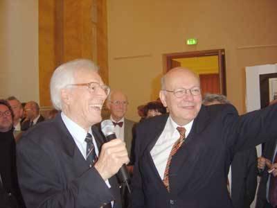 Zwei Männer lachen. Einer hält ein Mikro. Ein anderer zeigt auf etwas. Im Hintergrund stehen weitere Menschen.