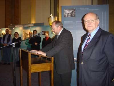 Ein Mann steht am Rednerpult für eine Ausstellungseröffnung. Andere hören ihm zu. Im Vordergrund schaut ein anderer Mann direkt in die Kamera.
