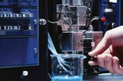 Man sieht eine Hand, die einen Hebel an einer technischen Maschine betätigt.