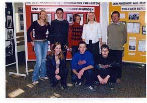 Gruppenfoto von Schülerinnen und Schülern vor Plakatwänden gemeinsam mit ihrem Lehrer.