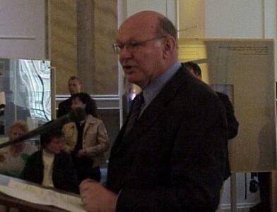 Ein älterer Herr steht am Rednerpult und spricht in ein Mikrofon, andere Menschen hören ihm zu.