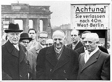 """Schwarz Weiß Foto von einer Gruppe von Männern vor dem Brandenburger Tor. Hinter ihnen ein Plakat auf dem steht """"Achtung! Sie verlassen nach 40m West-Berlin""""."""