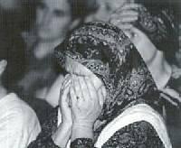Schwarz Weiß Foto einer alten Frau mit Kopftuch, die ihren Kopf in die Hände legt.