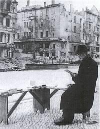 Schwarz-weiß-Foto. Ein alter Mann sitzt vor zerbombten Häusern auf einer Bank und verkauft Bücher.