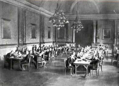 Schwarz Weiß Foto. Zwei lange Tafeln, daran sitzen Männer. Man sieht einen Saal mit riesigen Kronleuchtern.