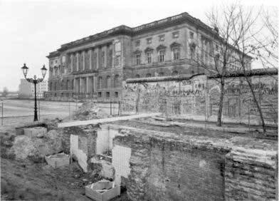 Schwarz Weiß Foto. Außenaufnahme des Abgeordnetenhaus. Man sie die Reste der Mauer im Vordergrund.