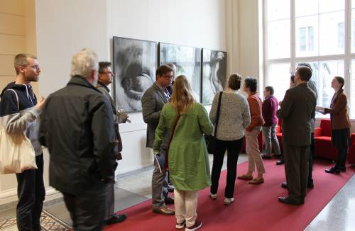 Eine Gruppe von Besucherinnen und Besuchern schauen sich Bilder im Abgeordnetenhaus an.