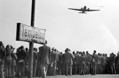 """Schwarz Weiß Foto einer Menschenmasse, die auf ein Flugzeug schaut. Im Vordergrund ein Schild auf dem steht """"Tempelhof""""."""