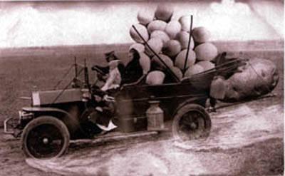 Fotomontage. Eine dreiköpfige Familie fährt mit einem alten Auto über ein Feld, auf der Ladefläche liegen riesige Kartoffeln.