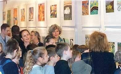 Junge Kinder und Erwachsene schauen sich eine Ausstellung an.