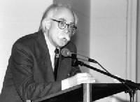 Schwarz Weiß Foto eines Mannes am Rednerpult. Er hat weiße Haare und einen weißen Schnurrbert.