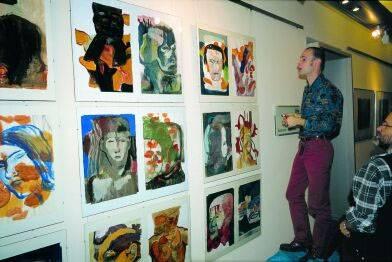 Zwei Männer schauen sich diverse Gemälde an.