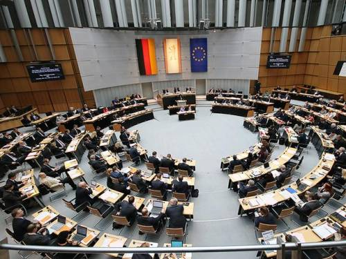 Blick von der Besuchertribüne in den Plenarsaal. An fast jedem Tisch sitzen Menschen.