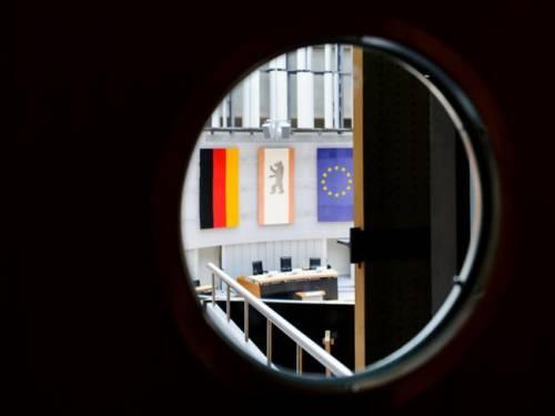 Blick durch ein Türfenster in den Plenarsaal.