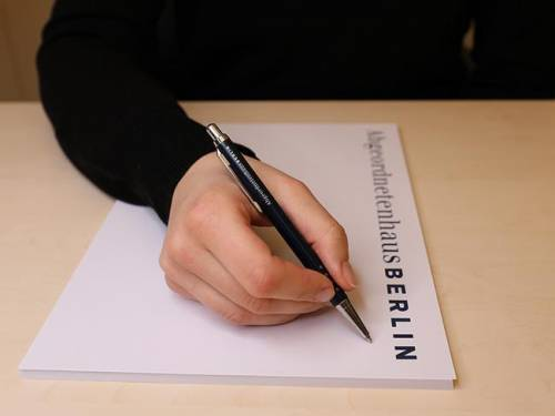 """Man sieht eine Hand, die einen Stift hält und auf einem Notizblock zu schreiben beginnt. Auf dem Notizblock steht gedruckt """"Abgeordnetenhaus Berlin"""""""