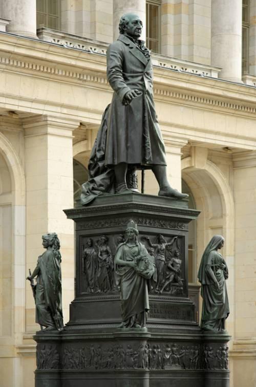 Statue auf dem Vorplatz des Abgeordnetenhaus Berlin. Ein älterer Mann im langen Mantel. Am Fuß der Säule 4 Frauen an jeder Ecke.