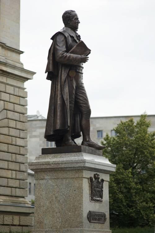 Statue auf dem Vorplatz des Abgeordnetenhaus Berlin. Ein älterer Mann im langen Mantel, der unter dem Arm ein Buch trägt.