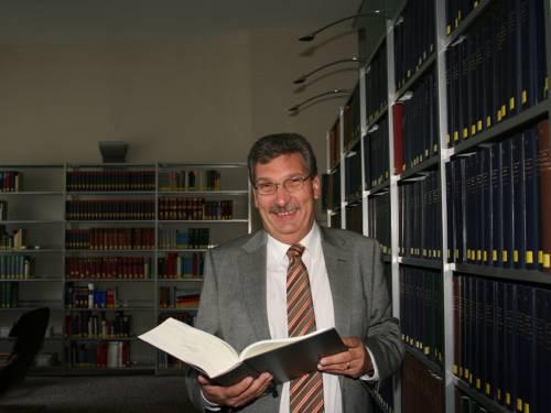 Ralf Wieland steht in der Bibliothek des Abgeordnetenhaus Berlin. In der Hand hat er ein aufgeklapptes Buch und lacht in die Kamera.
