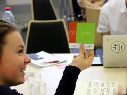 Ein Mädchen hält zwei Karten mit der Aufschrift Pro und Contra in die Höhe.