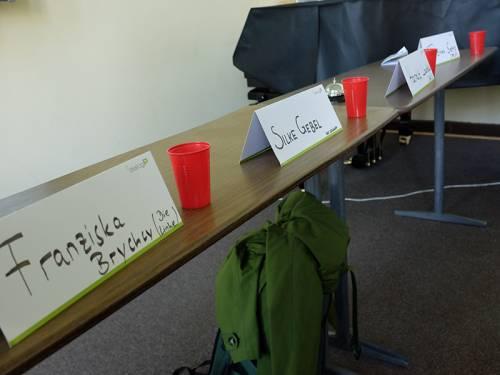 Namensschilder von Abgeordneten auf Schultischen.