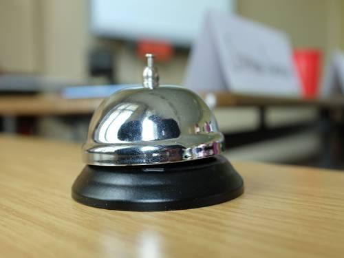 Eine Klingel steht auf einem Schultisch.