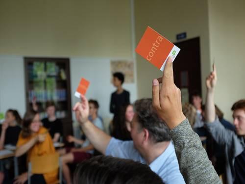 Eine Gruppe von Menschen sitzt in einem Klassenzimmer. Einige halten die Hände hoch mit einer Karte auf der steht Pro oder Contra.