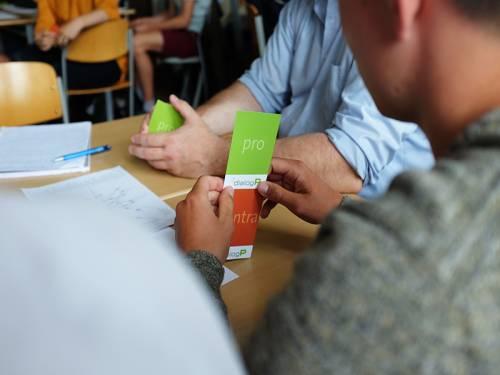 Blick über die Schulter einer Person, die an einem Schultisch sitzt. In der Hand hält sie Karten mit den Worten Pro und Contra.