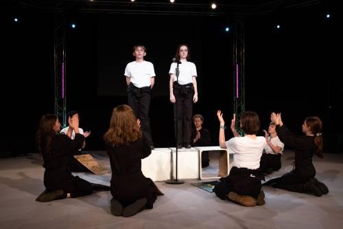 Eine Gruppe junger Schüler trägt etwas auf einer Bühne vor. Ein Junge und ein Mädchen stehen auf Podesten. Die restlichen Schüler knien um sie herum und klatschen.