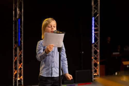 Ein junges Mädchen steht vor einem Mikofon. Sie hält ein Blatt in der Hand, von dem sie abliest.