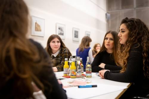Ein paar junge Frauen sitzen an einem Tisch und unterhalten sich.