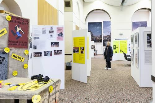 Eine ältere Frau schaut sich eine Ausstellung an.