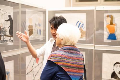 Ein Jugendlicher erklärt einer älteren Dame eine Zeichnung in einer Ausstellung.