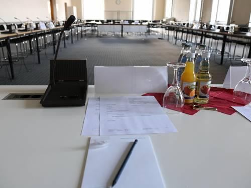 Blick in einen Sitzungssaal von einem Sitzplatz aus. Auf dem Tisch liegen Papiere sowie kleine Getränkeflaschen, ein Glas und ein Mikrofon.