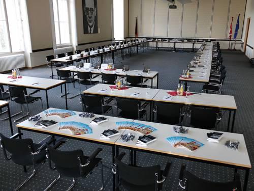 Blick in einen Sitzungsaal, der für eine Sitzung vorbereitet ist. Auf den Tischen stehen Getränke und Notizblöcke. Auf den vorderen Tischen liegen Infomaterialien.