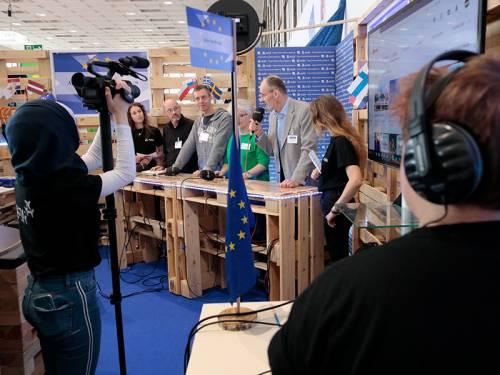 Abgeordnete im Gespräch mit jungen Menschen in einem mobilen Fernsehstudio aus Europaletten. Man sieht Jugendliche, die filmen.