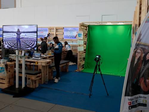 Ein aus Holzpaletten gefertigtes mobiles Fernsehstudio. Daneben ein Bereich mit einem grünen Hintergrund, der als Greenscreen dient. Junge Menschen sind im Fernsehstudio.