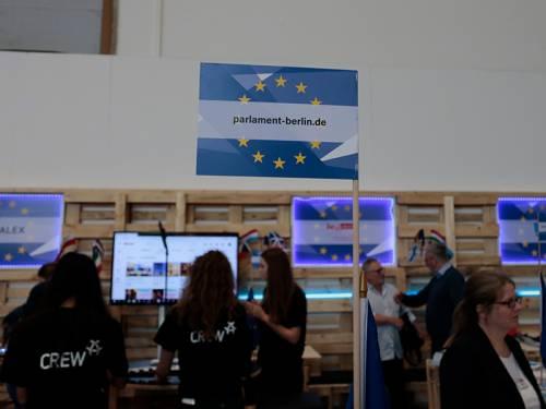 """Im Fokus ist eine kleine Flagge mit der Aufschrift """"parlament-berlin.de"""". Im Hintergrund sieht man Menschen in einem mobilen Fernsehstudio aus Holzpaletten."""