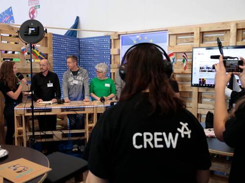 In einem mobilen Fernsehstudio aus Holzpaletten werden mehrere Menschen interviewt.