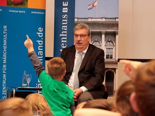 Ralf Wieland sitzt auf einem Stuhl. Vor ihm hocken Kinder auf dem Boden. Ein Junge im grünen T-Shirt steht auf und hebt seine Hand, um eine Frage zu stellen.