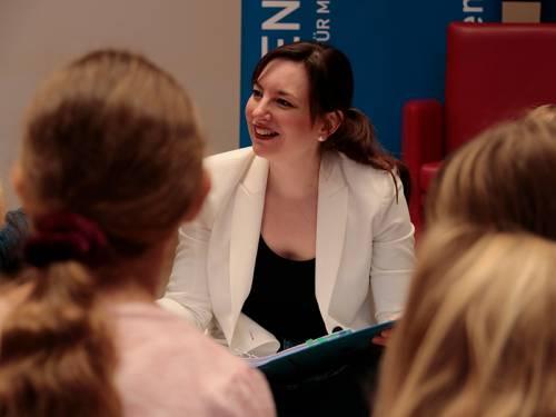 Eine junge Frau lacht Kindern im Publikum zu, sie hat ein Märchenbuch auf dem Schoß.