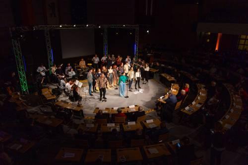 Menschen singen und musizieren auf einer Bühne.